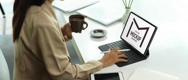 Vrouwelijke kantoormedewerker koffiekopje te houden tijdens het typen