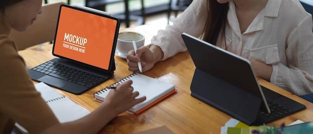 Vrouwelijke studenten bespreken hun project tijdens het werken met mockup-tablet