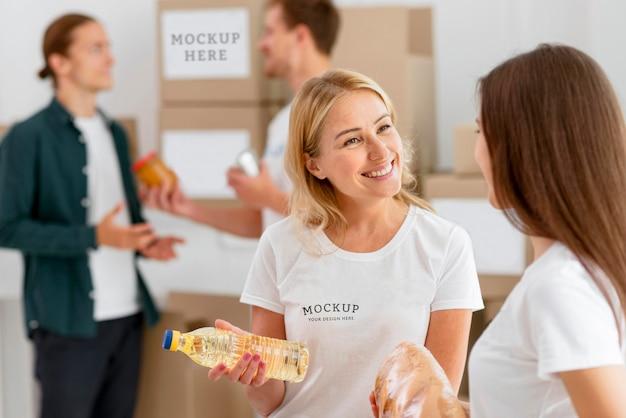 Vrouwelijke vrijwilligers bereiden donatieboxen en man die voedsel doneert
