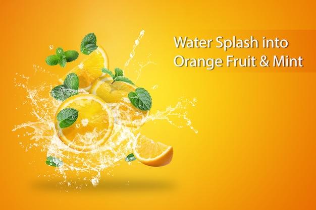 Water spatten op gesneden sinaasappel over oranje.