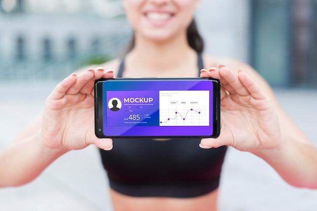 Wazig fit vrouw met mobiele telefoon mock-up