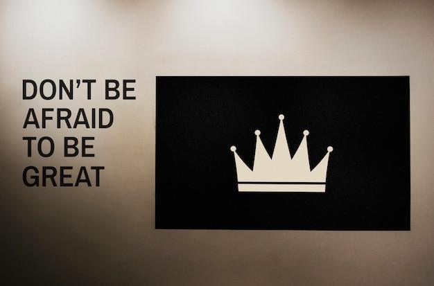 Wees niet bang om groots te worden aangehaald op een muur naast een mockup met kroonplaten