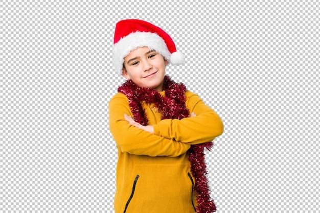 Weinig jongen het vieren kerstmisdag die een geïsoleerde santahoed draagt die zeker voelt, gekruiste wapens met vastberadenheid.