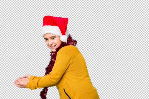 Weinig jongen het vieren kerstmisdag die een geïsoleerde santahoed draagt houdend een exemplaarruimte op een palm.