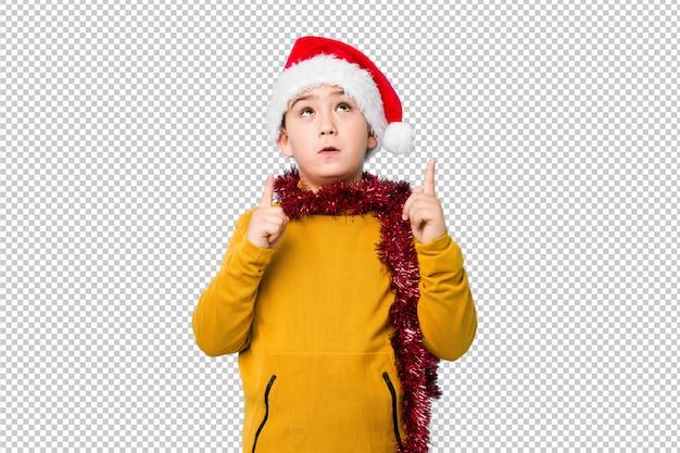 Weinig jongen het vieren kerstmisdag die een geïsoleerde santahoed draagt richtend bovenkant met geopende mond.