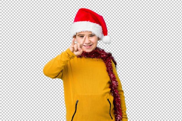 Weinig jongen het vieren kerstmisdag die een geïsoleerde santahoed draagt tonend een hoornengebaar als revolutieconcept.
