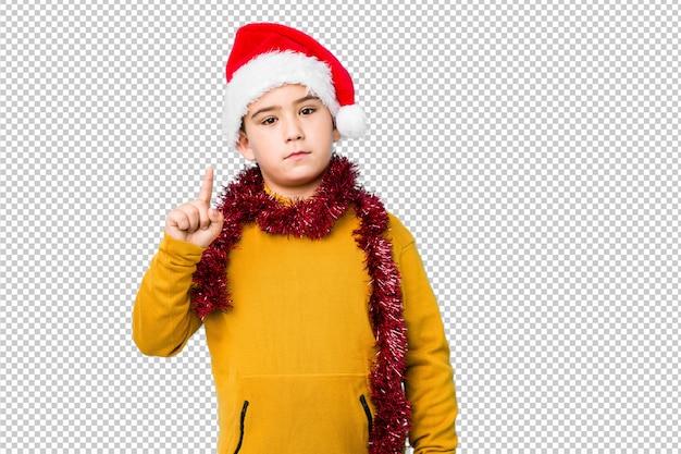 Weinig jongen het vieren kerstmisdag die een geïsoleerde santahoed draagt tonend nummer één met vinger.
