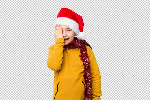 Weinig jongen het vieren kerstmisdag die een santahoed draagt isoleerde hebbend pret die de helft van gezicht behandelen met palm.