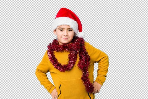 Weinig jongen het vieren kerstmisdag die een santahoed draagt isoleerde het zekere houden van handen op heupen.