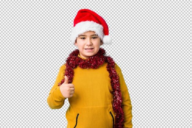 Weinig jongen het vieren kerstmisdag die een santahoed draagt isoleerde omhoog het glimlachen en het opheffen van duim