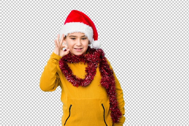 Weinig jongen het vieren kerstmisdag die een santahoed draagt isoleerde vrolijk en zeker tonend ok gebaar.
