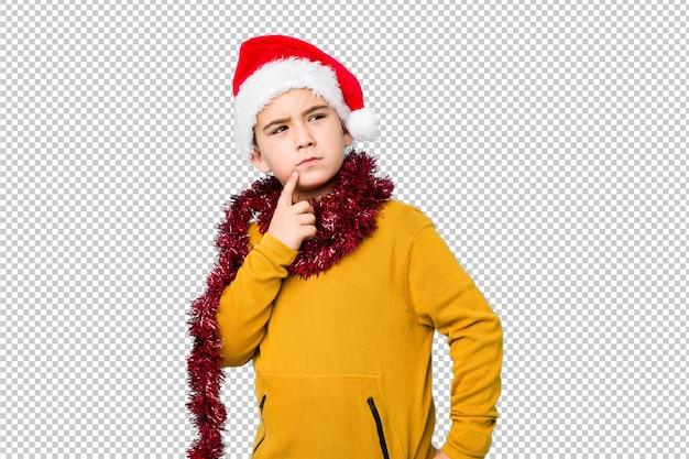 Weinig jongen het vieren kerstmisdag die een santahoed draagt isoleerde zijdelings het kijken met twijfelachtige en sceptische uitdrukking.