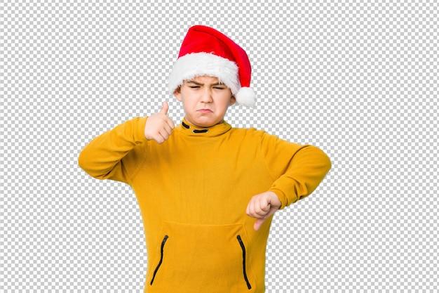 Weinig jongen het vieren kerstmisdag die een santahoed dragen die duimen tonen en duimen neer, moeilijk concept