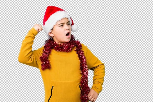 Weinig jongen het vieren kerstmisdag die een santahoed dragen isoleerde het opheffen van vuist na een overwinning, winnaarconcept.