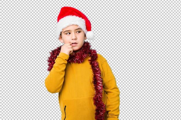 Weinig jongen het vieren kerstmisdag die een santahoed dragen isoleerde ontspannen denkend aan iets bekijkend een exemplaarruimte.