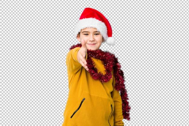 Weinig jongen het vieren kerstmisdag die een santahoed dragen isoleerde uitrekkende hand bij camera in groetgebaar.