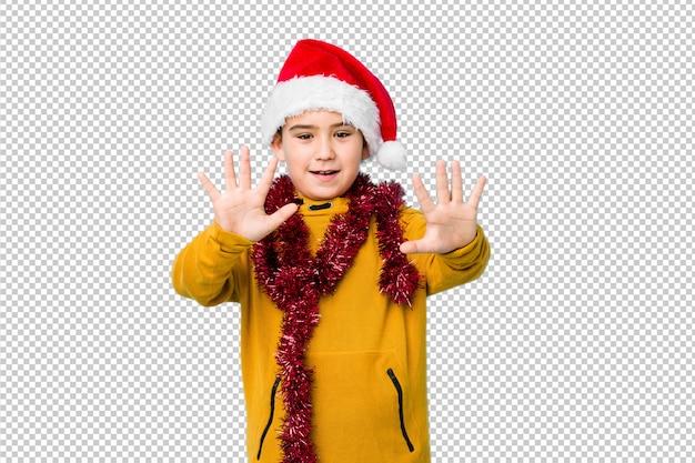 Weinig jongen het vieren kerstmisdag die geïsoleerd een santahoed toont tonend nummer tien met handen.