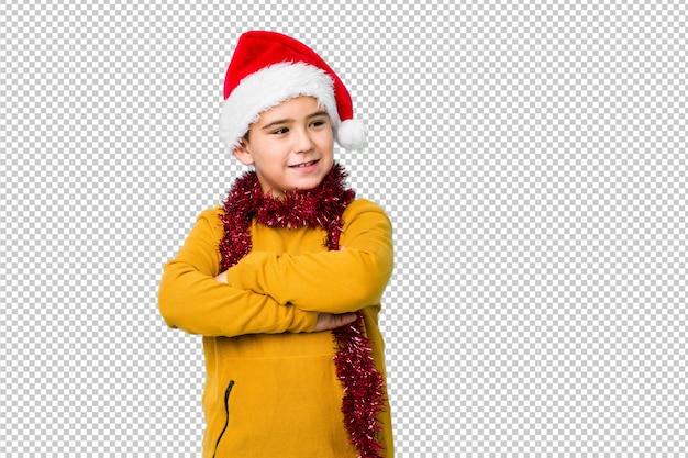 Weinig jongen het vieren kerstmisdag die geïsoleerde een santahoed draagt glimlacht zeker met gekruiste wapens.