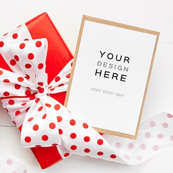 Wenskaart mockup met rode geschenkdoos met strik op witte achtergrond