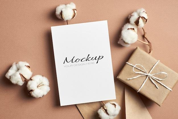 Wenskaart of uitnodigingskaartmodel met geschenkdoos en katoenen bloemendecoraties op beige