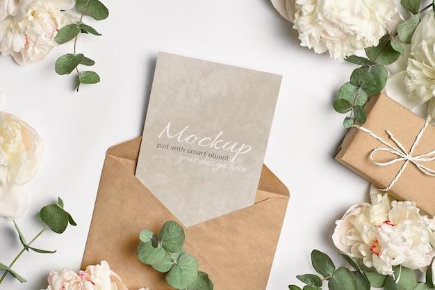 Wenskaart of uitnodigingsmodel met envelop, geschenkdoos en witte pioenrozen met eucalyptustakjes