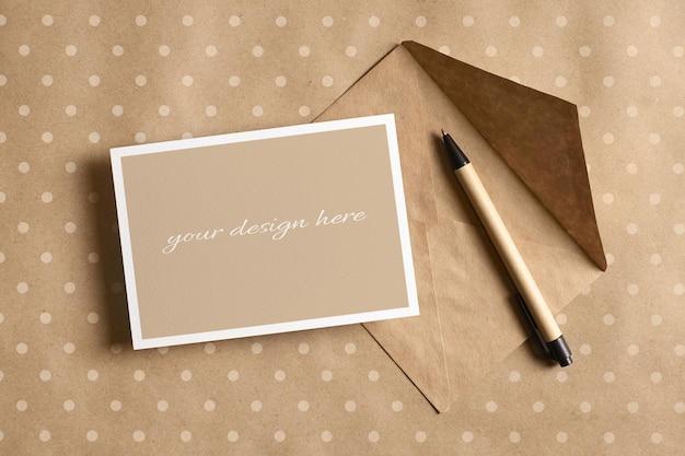 Wenskaart stationaire mockup met envelop en pen op ambachtelijk papier