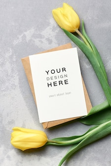 Wenskaartmodel met envelop en gele tulp bloemen op grijs