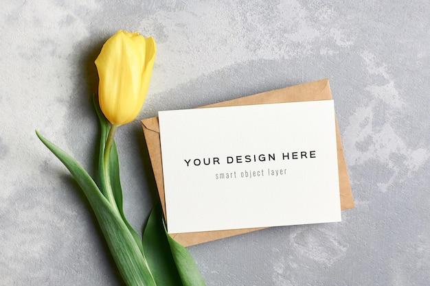 Wenskaartmodel met envelop en gele tulpenbloem op grijs