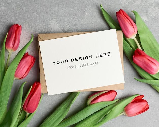 Wenskaartmodel met envelop en rode tulp bloemen op grijs