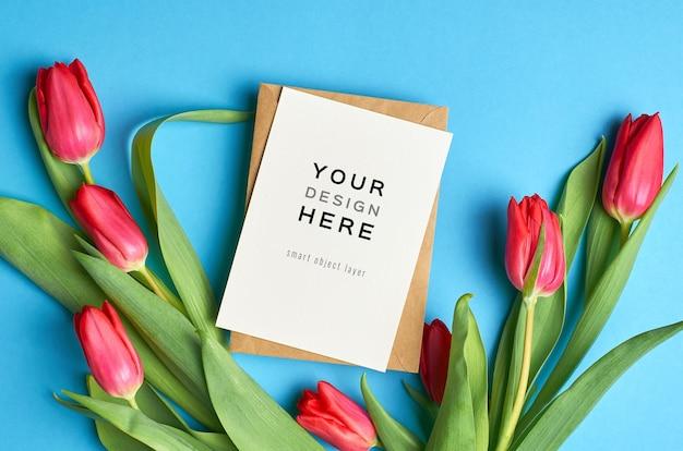 Wenskaartmodel met envelop en rode tulp bloemen