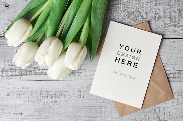 Wenskaartmodel met envelop en tulp bloemen op houten achtergrond