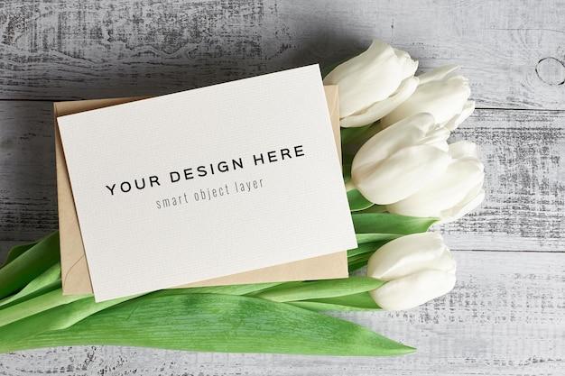 Wenskaartmodel met envelop en tulp bloemen op houten