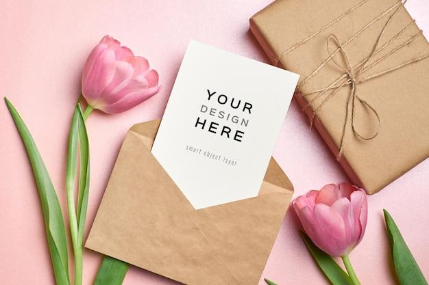 Wenskaartmodel met envelop, geschenkdoos en roze tulp bloemen