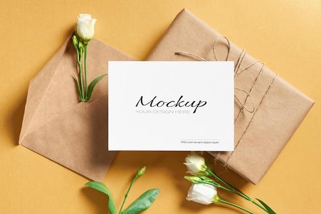 Wenskaartmodel met envelop, geschenkdoos en witte eustomabloemen op goud