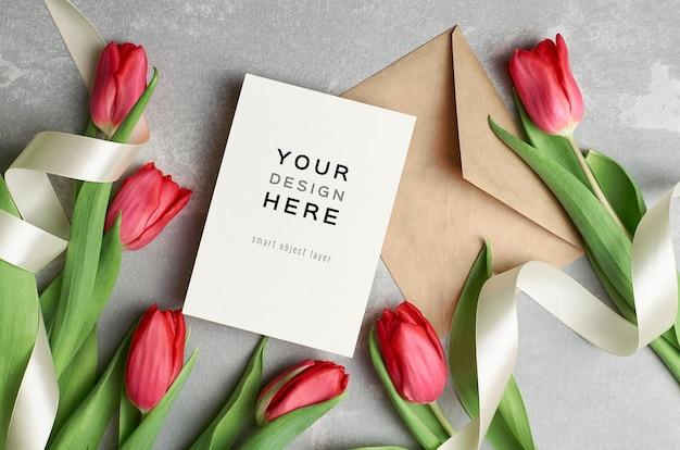Wenskaartmodel met envelop, linten en rode tulpenbloemen