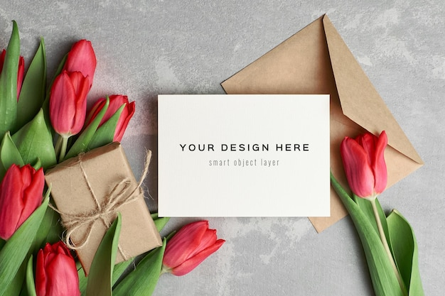 Wenskaartmodel met geschenkdoos en rode tulp bloemen