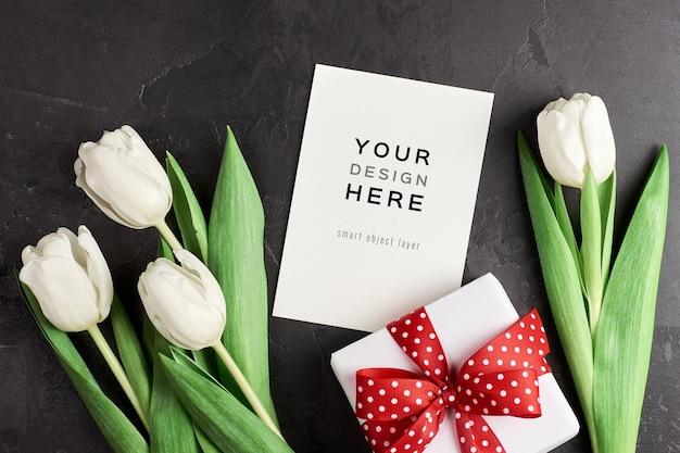 Wenskaartmodel met geschenkdoos en witte tulp bloemen op zwart