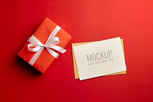 Wenskaartmodel met geschenkdoos op rode achtergrond