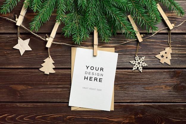 Wenskaartmodel met houten kerstversieringen en dennentakken