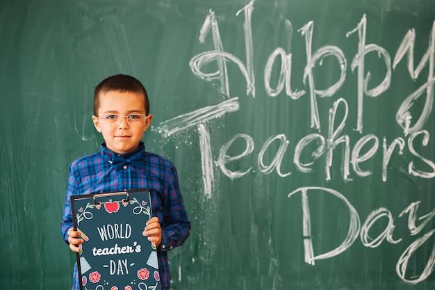Werelddag leraar mockup met jongen klembord te houden