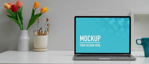 Werkruimte met digitale laptop mockup, koffiekopje en benodigdheden