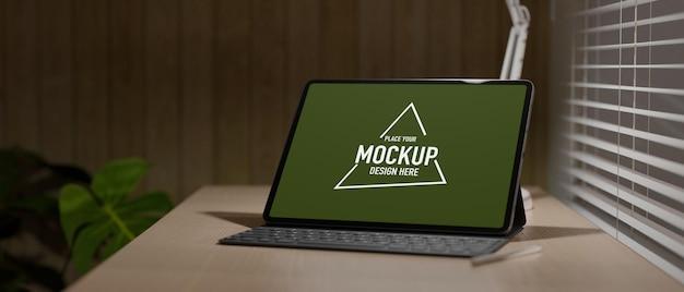 Werkruimte met grafisch tablet met toetsenbord onder licht op houten tafel naast het raam