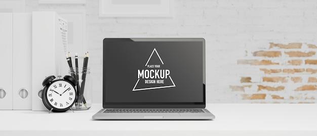 Werkruimte met laptop leeg scherm klok potloden bestandsmap op witte tafel witte bakstenen muur