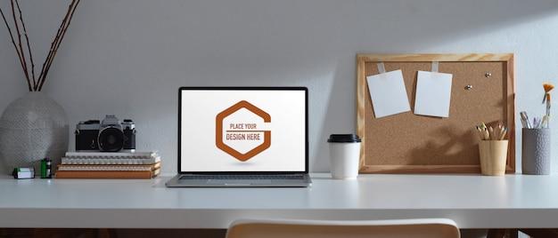 Werktafel met mockup-laptop, briefpapier en camera