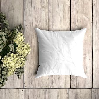 Wit kussensloopmodel op een houten plank met bloemendecoratie