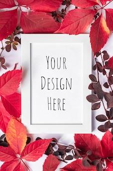 Wit leeg afbeeldingsframe mockup met rode en oranje herfstbladeren