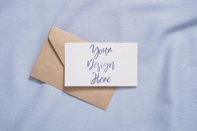 Witte blanco papieren kaart en envelopmodel op blauw gekleurd textiel