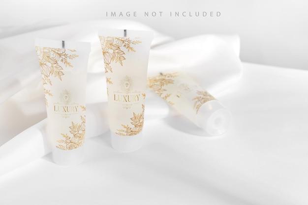 Witte buis voor cosmetische producten op standaard met stoffen draperie.
