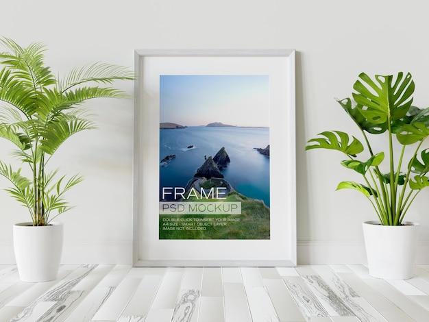 Witte fotolijst leunend op muur mockup