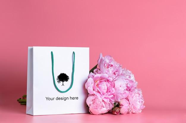 Witte geschenktas met een boeket pioenrozen op een roze